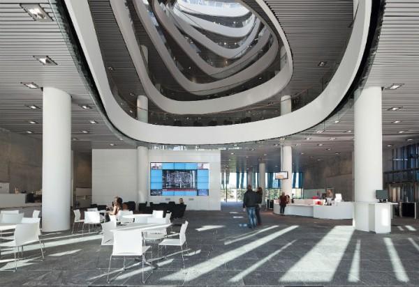 9-этажное кубическое здание поражает удивительно цельным и органичным интерьером. Большой спиральный атриум визуально объединяет этажи и проводит солнечный свет со стеклянной крыши