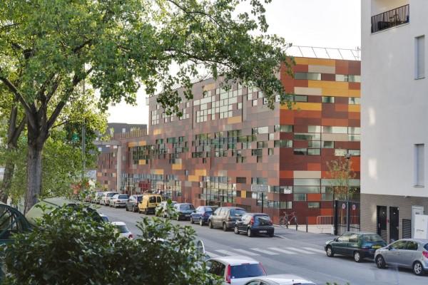 Со стороны улицы объект выглядит как двухэтажное здание, обшитое разноцветными деревянными панелями